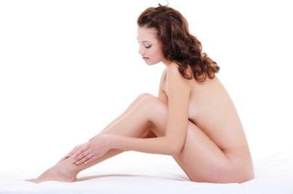 Nackte Frau streicht über Ihre enthaarten Beine
