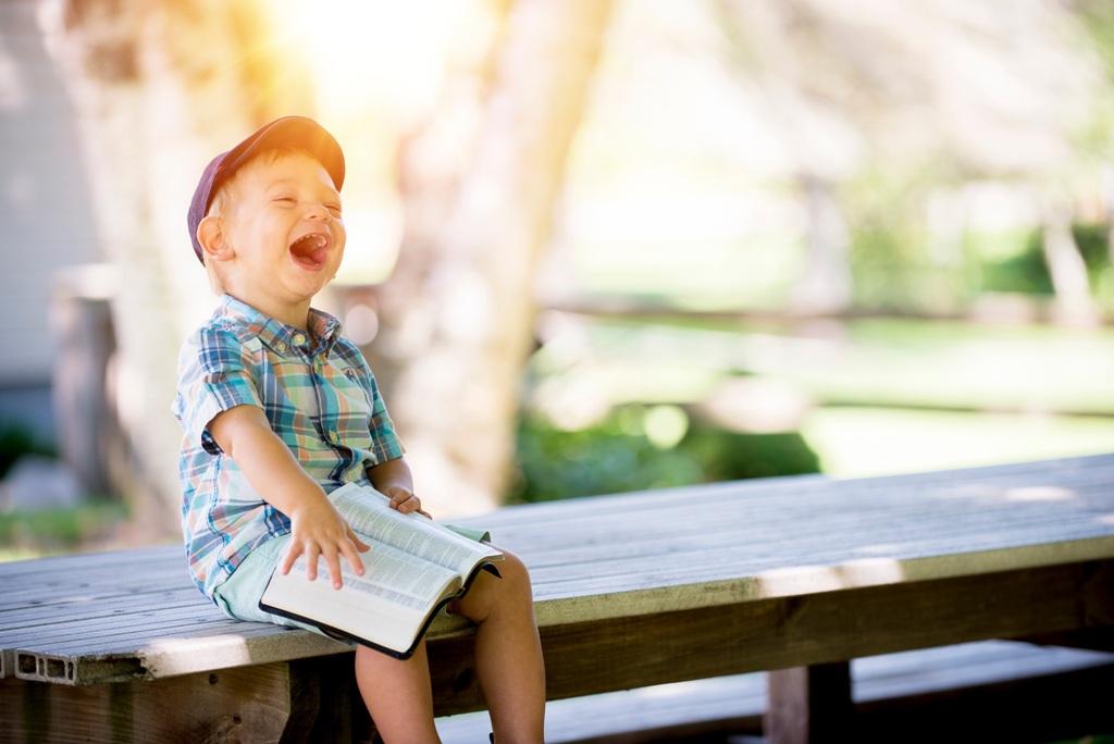 Kind mit Buch lacht