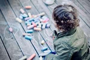 Kind malt Bild mit Kreide